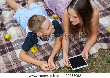 Young sister and brother with freckles on their faces lying down on plaid and using tablet in park. looking to each other and smiling. top view. - stock photo