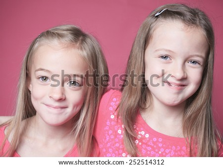 young sister girl poses for a picture isolated on pink - stock photo