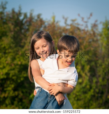 Young sister hugs her brother outdoors. - stock photo