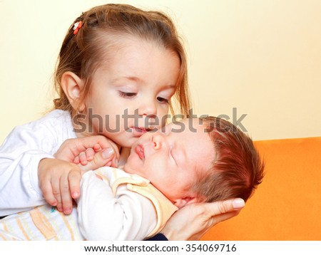 Young sister kissing her newborn adorable brother - stock photo