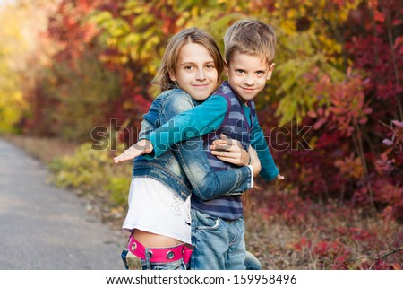Young sister with little brother in the autumn park. Family Portrait. - stock photo