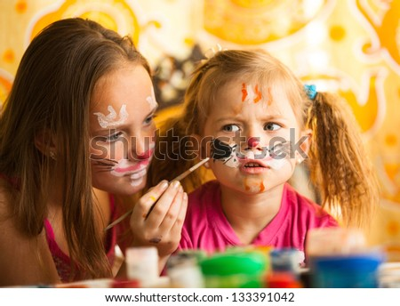 Young sisters playing with painting - stock photo