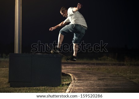 Young Skateboarder doing a Frontside Boardslide trick at Night - stock photo