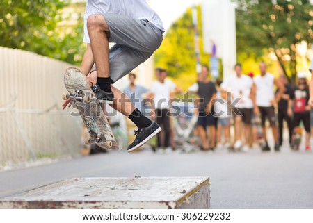 Young skateboarder skateboarding on an object in street. Skateboarding legs doing trick ollie at skate park. Group of friends cheering in the background. - stock photo