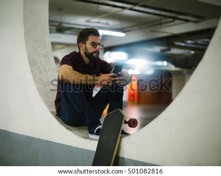 Young skateboarder using mobile phone