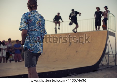Young skateboarders in skatepark jumping in the halfpipe on beach. Group of friends standing in a row with skateboards in hands. Urban life wallpaper. Youth subculture - stock photo