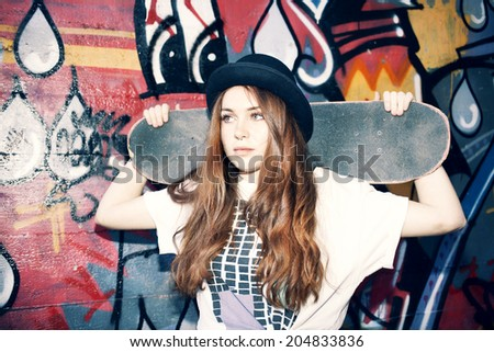 Young skater girl holding her skate in an urban place - stock photo
