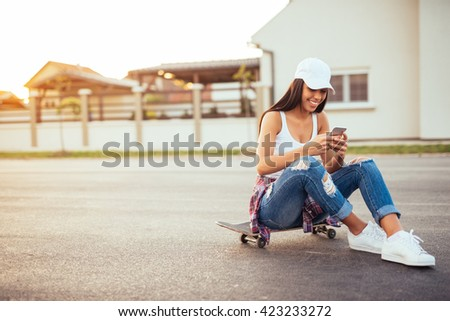 Young skater girl using a mobile phone. - stock photo