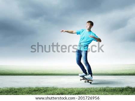 Young skater in jeans riding on road - stock photo