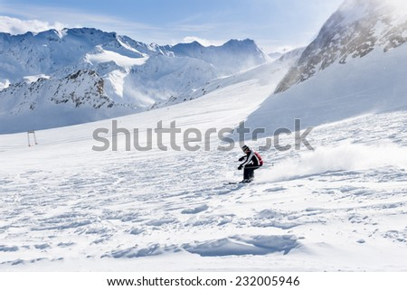 Young skier downhill on the ski slope - stock photo