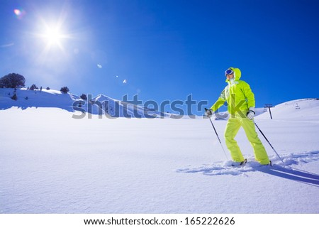Young skier in bright clothes the first one to concur new snow terrain - stock photo