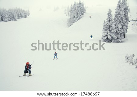 Young skiers on the slope in the light fog - stock photo