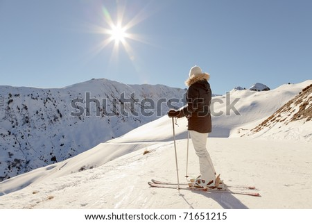 Young skiing woman standing in snow mountain landscape with blue sky. Sunshine. Resting. Enjoying the view. Alps. France.
