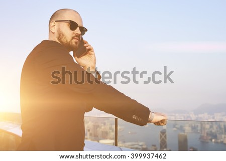 Young skilled man financier in fashionable sunglasses having cell telephone conversation, while is standing on a roof tall skyscraper. Successful male CEO is calling via mobile phone during work break - stock photo