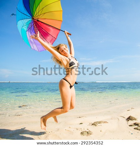 Young skinny girl in blue shorts with colourful rainbow umbrella jumps on the beach with clear blue sky and ocean on background - stock photo