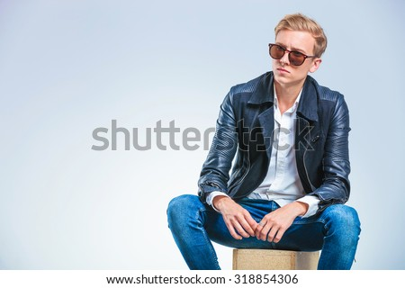 young skinny man wearing sun glasses and leather jacket while sitting on a box - stock photo