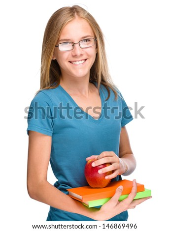 Young skinny student girl is holding exercise books and apple, isolated over white - stock photo