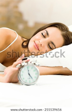 Young sleeping woman with alarmclock on the bed - stock photo