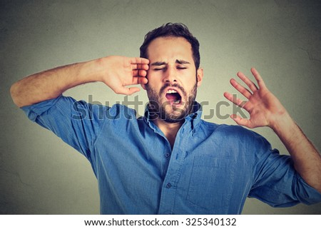 Young sleepy man yawning stretching arms back isolated on gray wall background. Sleep deprivation, burnout, laziness concept