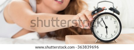 Young sleepy woman trying to turn off the alarm clock. Early morning waking up. Letter box format. Letter box format - stock photo