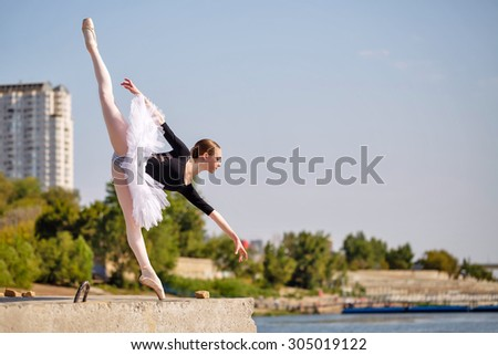 Young slim ballerina in tutu dancing on the pier of the city. Summer day. The concept contemporary ballet. Performance on the street. Arabesque