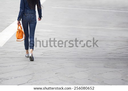 Young slim casual woman with orange leather bag, back view - stock photo