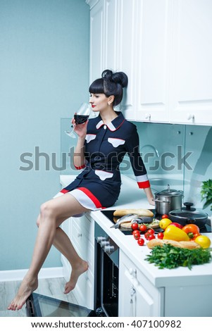 Young slim girl in the kitchen. Girl drinking wine sitting on a cabinet at the stove. Household chores. - stock photo