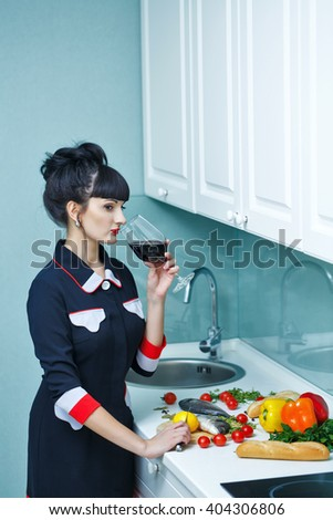 Young slim girl in the kitchen. The girl is drinking wine before dinner. Household chores . - stock photo