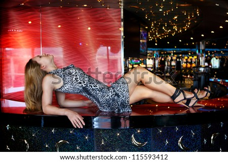 young slim girl lying on a bar counter - stock photo