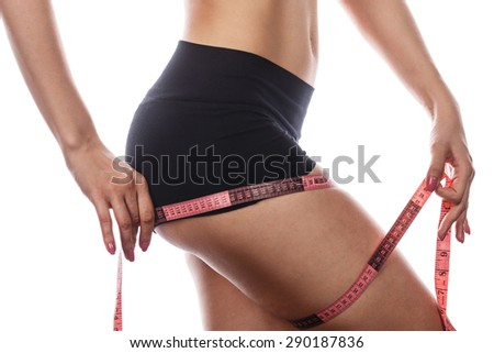 Young slim girl measures the volume of the hip belt. Beautiful female legs. Isolated on white background. Concept sports lifestyle and diet. - stock photo