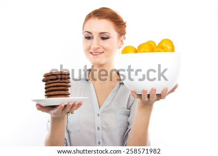 Young slim girl with tangerines and chocolate chip cookies. Portrait of a woman on a diet. Tasty and useful. Counting calories. Portrait of a girl isolated on a white - stock photo