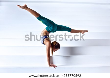 Young slim gymnast woman in sports clothing standing upside down on bright white stairs. - stock photo