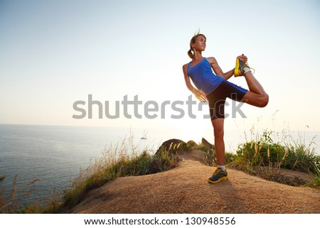 Young slim lady doing stretching exercises on a rural path with grass - stock photo