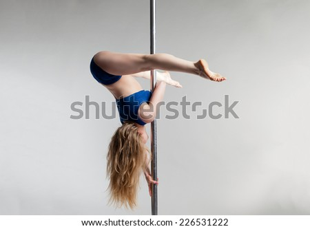Young slim pole dance woman exercising over light gray bacground - stock photo