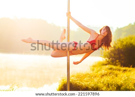 Young slim pole dance woman on nature background. - stock photo