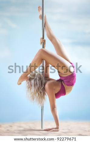 Young slim pole dance woman on summer beach. - stock photo