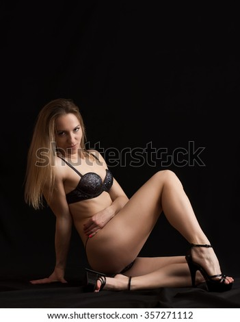 Young slim pole dance woman posing over dark background. - stock photo