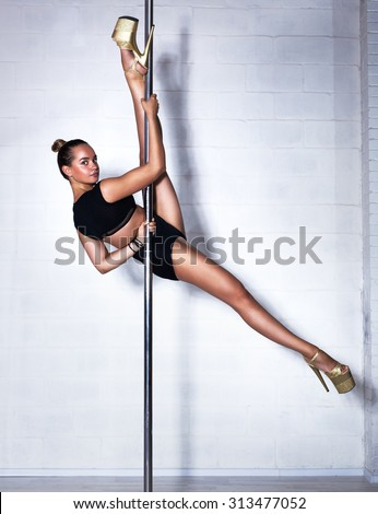 Young slim sexy pole dance woman in black clothing. Bright white interior.
