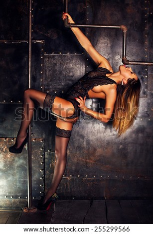 Young slim sexy pole dance woman in black lingerie on dark metallic wall background. - stock photo