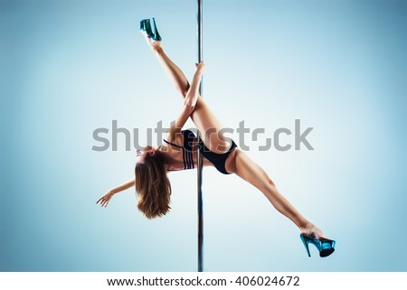 Young slim sexy pole dance woman on white and blue background