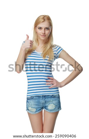 Young slim tanned female in denim shorts giving you thumb up, isolated on white - stock photo