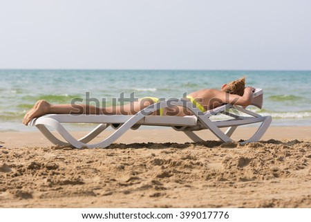 Young slim tanned woman on sea beach lying on deckchair face down - stock photo
