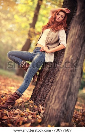Young slim woman autumn portrait. Red colors. - stock photo