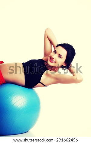 Young slim woman excercising on ball