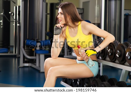 Young slim woman exercising in a gym - stock photo