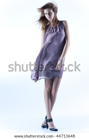 Young slim woman in fluttering dress. Soft blue tint. - stock photo