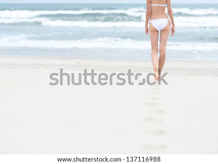 Young slim woman in white swimsuit walking to sea or ocean leaving footprints on soft sand. Blue ocean waves with foam in background. Bathing or sunbathing on beach. Holidays and vacations in summer.