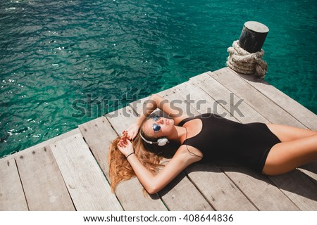 young slim woman laying on pier, Mediterranean Sea, azure water, sunny, tanned skin, listening music, headphones, black swimsuit, sexy body, sunbathing, tropical vacation, relaxed, sunglasses - stock photo