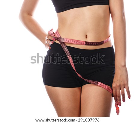 Young slim woman measuring waist circumference, after a diet. Isolated on white background. The concept of excess weight loss and healthy eating. - stock photo