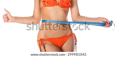 Young slim woman measuring waist circumference and shows a thumbs up after a diet. Isolated on white background. The girl in swimsuit. The concept of excess weight loss and healthy eating. - stock photo